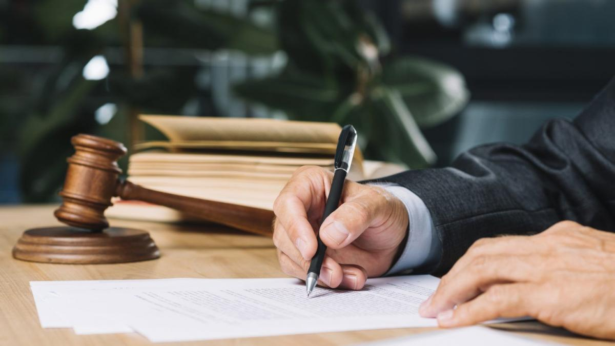man signing document inside law firm